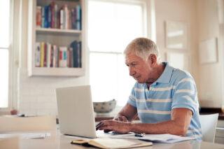 photo - Senior Man Using Laptop at Home