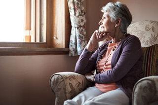 photo - Senior Woman Sitting Alone in Livingroom