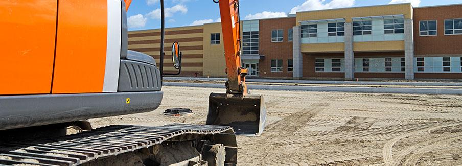 photo - Excavator and New School Building
