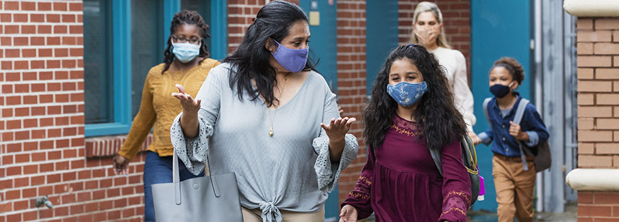 photo - Mothers with Children Walking Outside School Building, Wearing Masks