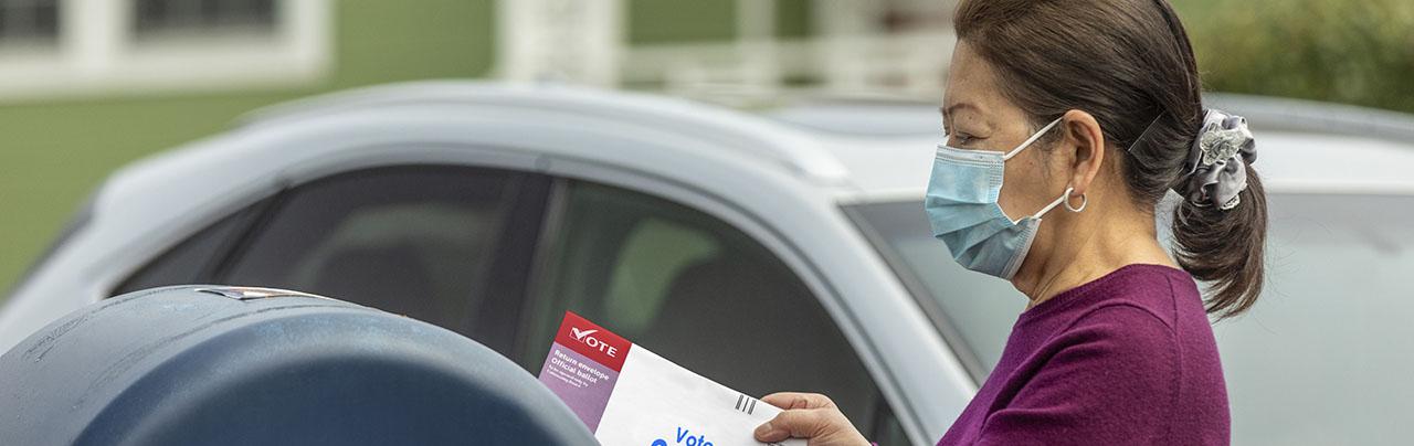 photo - Woman Wearing Mask at Mailbox Mailing in Ballot