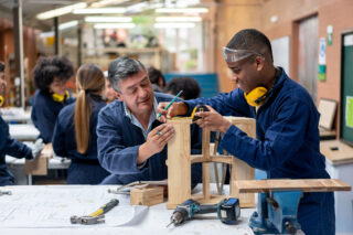 photo - Student Building Furniture with Help from Teacher