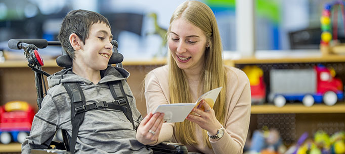 photo - Student in Wheelchair Being Read a Book