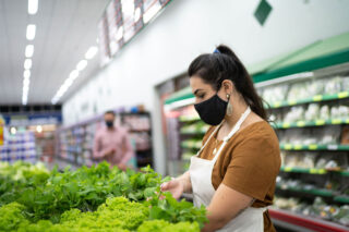 photo - Supermarket Worker Arranging Vegetables and Wearing Mask