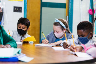 photo - Teacher and Students at Center Table in Classroom Wearing Masks
