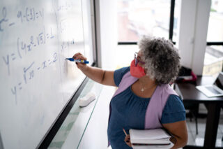 photo - Teacher Writing Equations on Whiteboard and Wearing Face Mask