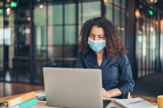 photo - Tech Worker Wearing Mask at Laptop