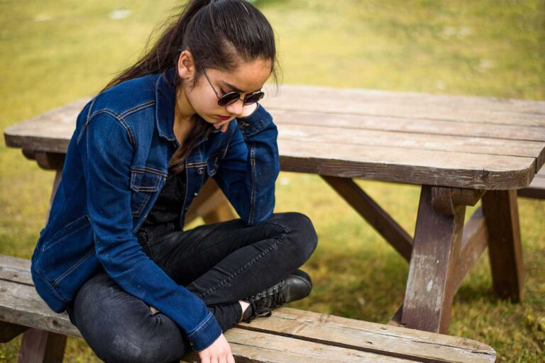photo - Teen Sitting at Picnic Table