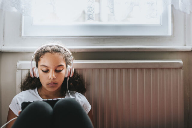 photo - Teenage Girl Listening with Headphones and Looking at Tablet