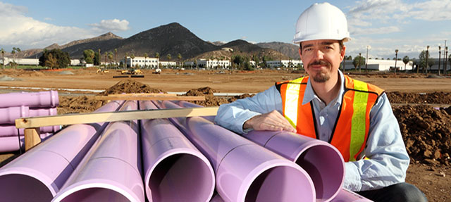 photo - Utility Worker Leans on Stacked Purple Pipe