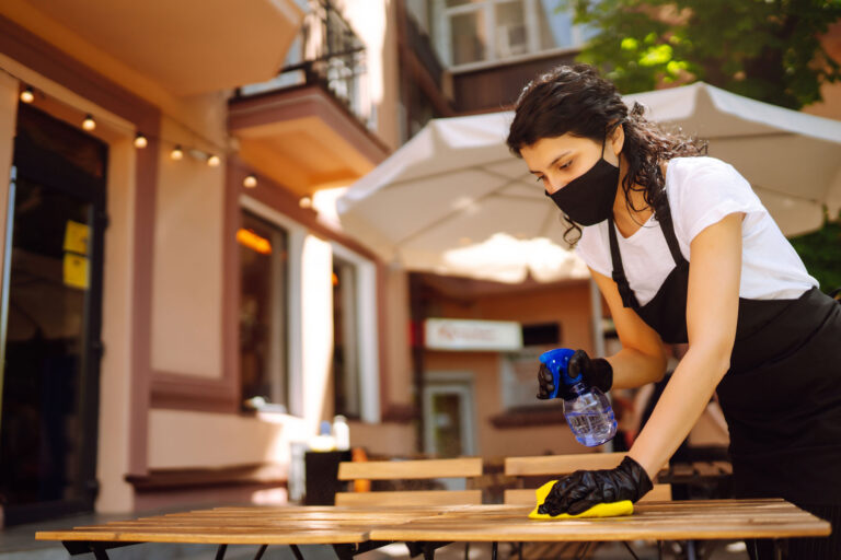 photo - Waitress Wearing Mask and Gloves, Cleaning Table on Cafe Patio