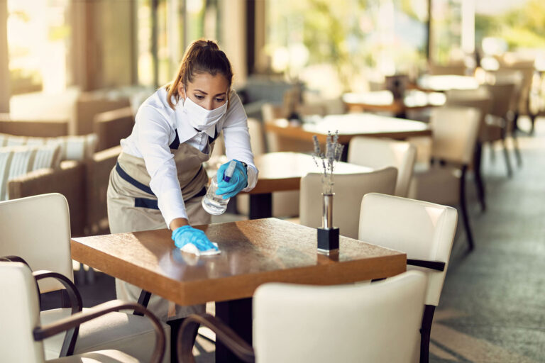 photo - Waitress Wearing a Mask and Gloves, Disinfecting Tables in a Restaurant