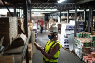 photo - Warehouse Worker Wearing Face Mask and Protective Workwear Checking Products Using Tablet