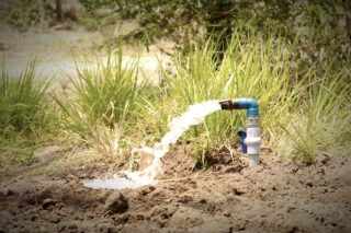 photo - Water Being Pumped Out on Agricultural Land Using Pump and Motor