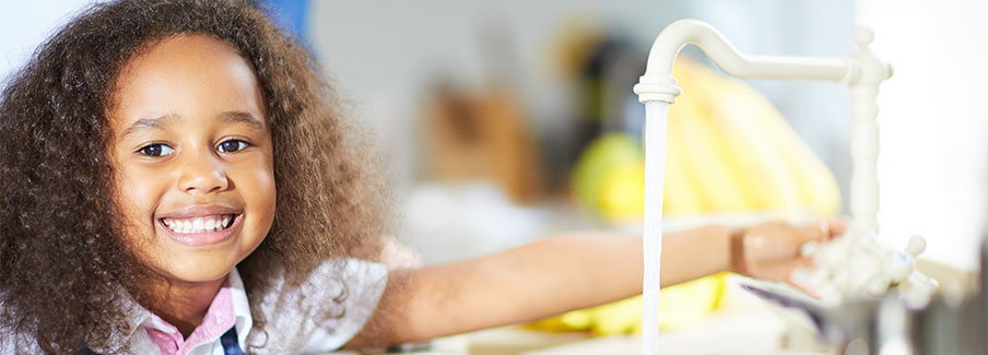 photo - Little Girl Turning on Tap in Kitchen
