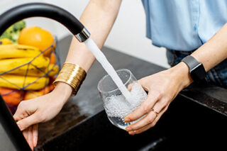 photo - Woman Filling Glass with Tap Water