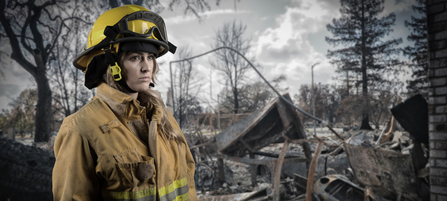 Photo of a female firefighter in a burned forest
