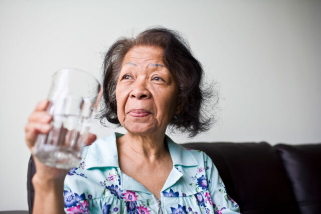 photo - Woman Holding a Glass of Water
