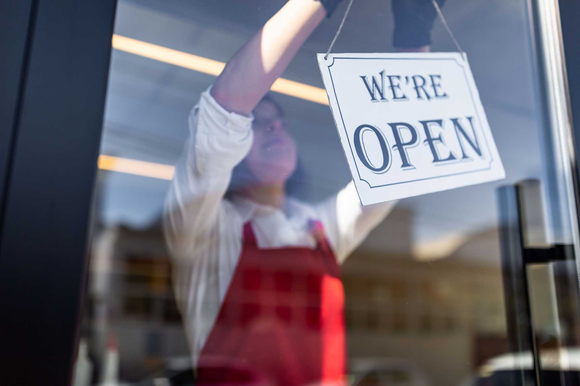 Woman Placing Open Sign In Store Getty 1279940677