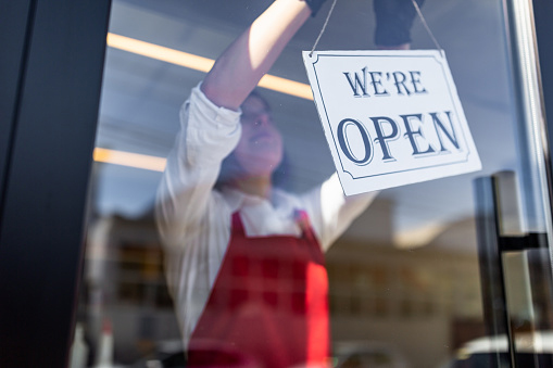 photo - Woman Placing Open Sign in Storefront