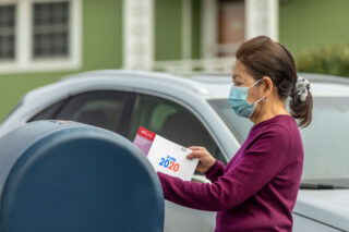 photo - Woman Wearing Mask at Mailbox, Mailing in Ballot