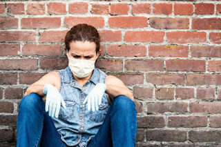 photo - Woman Wearing Protective Mask and Gloves, Looking Down and Sitting on Ground