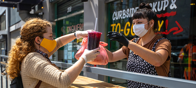 Photo of a restaurant worker handing customer takeout in masks