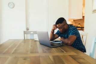 photo - Worried Man on Laptop at Home