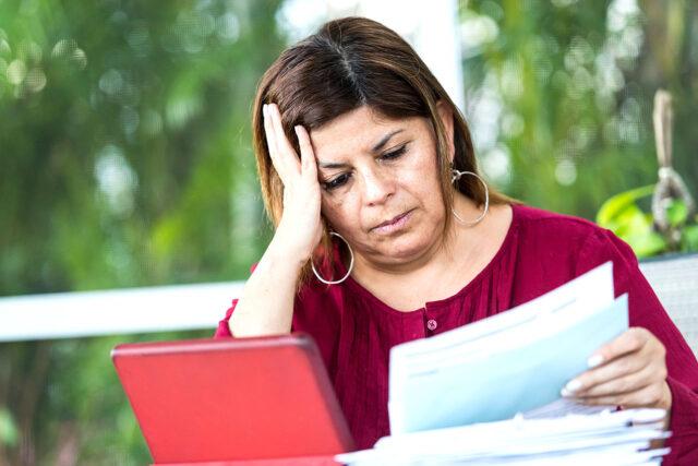 photo - Worried Woman Looking at Bills