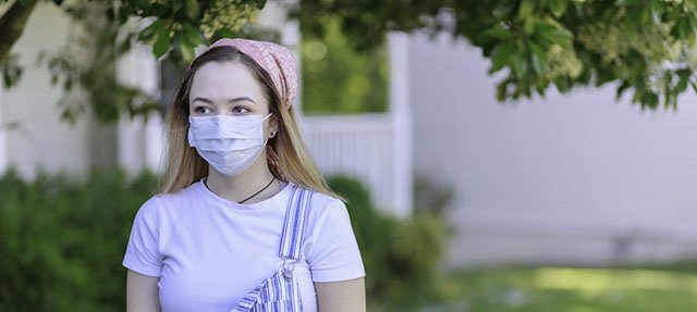 photo - Young Adult Wearing a Mask