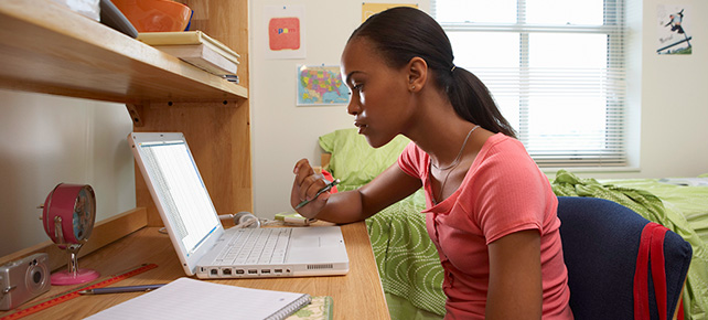 photo - Young African American Student Sitting At Desk On Laptop