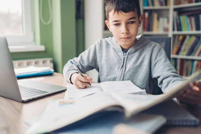 photo - Young Boy Doing Schoolwork at Home