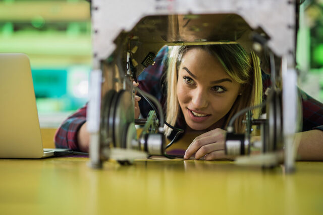 photo - Young Woman Examing Machinery