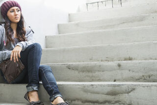 photo - Young Woman Sitting on Stairs