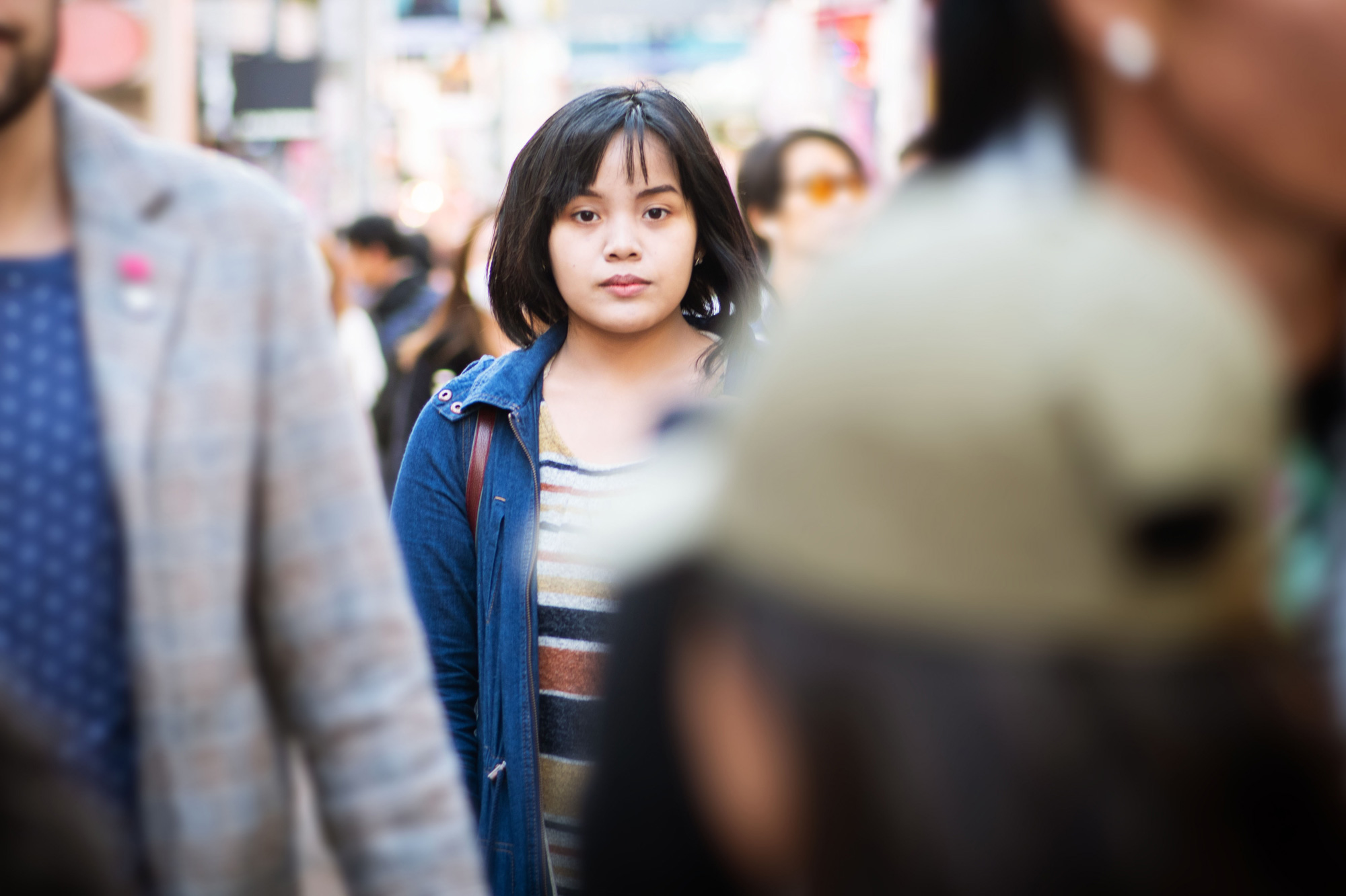 photo - Young Woman Standing in the Middle of a Crowded Street