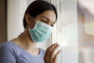 photo - Young Woman Wearing Mask and Looking Out Window